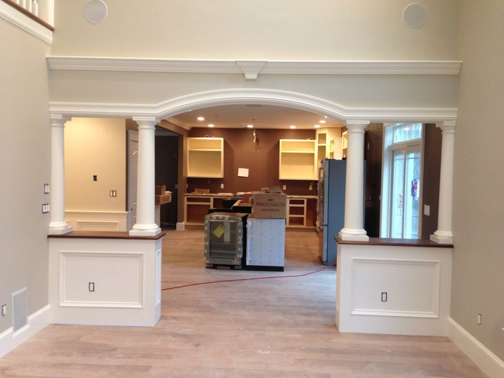 Arched opening with walnut half walls and columns for Archway designs for interior walls