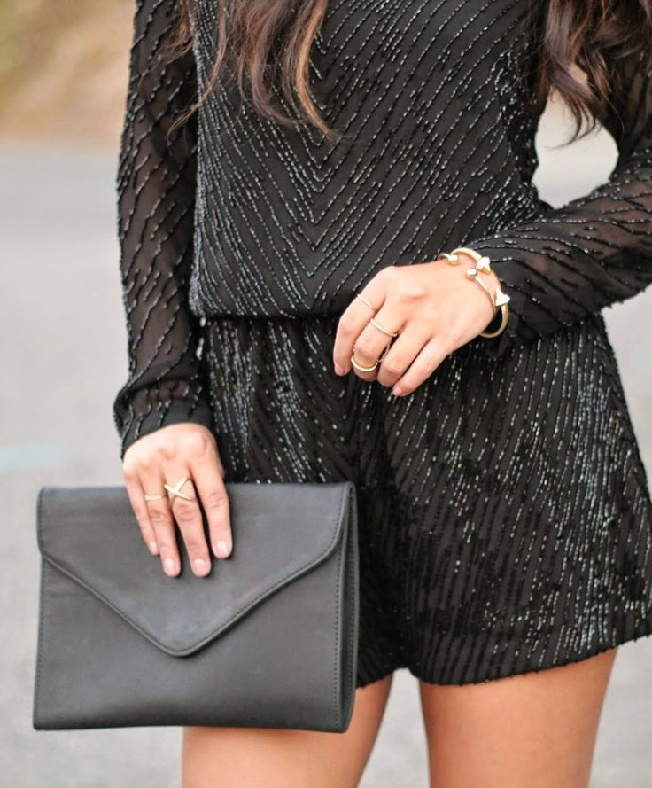 sequined romper and black clutch