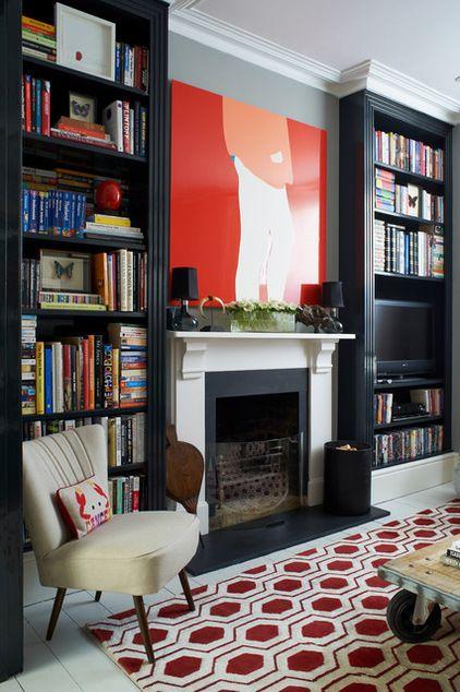 Near black floor to ceiling bookshelves frame the fireplace.