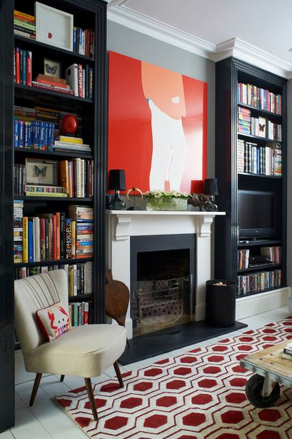 Near black floor to ceiling bookshelves frame the fireplace.