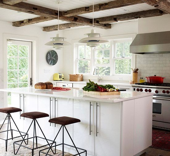 Neutral walls allow the furnishings, artwork, and exposed beams to be the stars of the show in this room. This cottage kitchen uses funky stools to add modern flair to the design and stand out against the white walls and cabinetry.