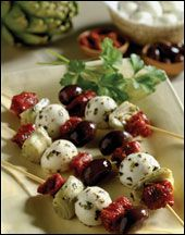 This fantastic summer time cold appetizer includes mild, delicious Mozzarella cheese that is threaded on a skewer along with chunks of sun-dried tomatoes, a wedge of tender artichoke heart, olives and basil leaves.