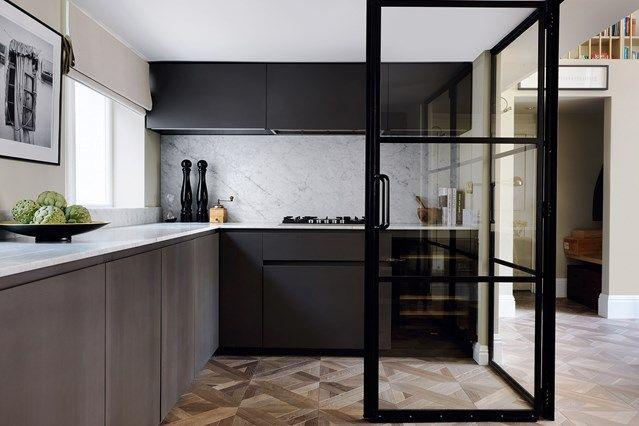 Modern Kitchen With Crittall Doors in Kitchen Design Ideas. Modern monochrome and minimalist kitchen with carrara marble worktops and splashbacks, veneer units and wooden floor.
