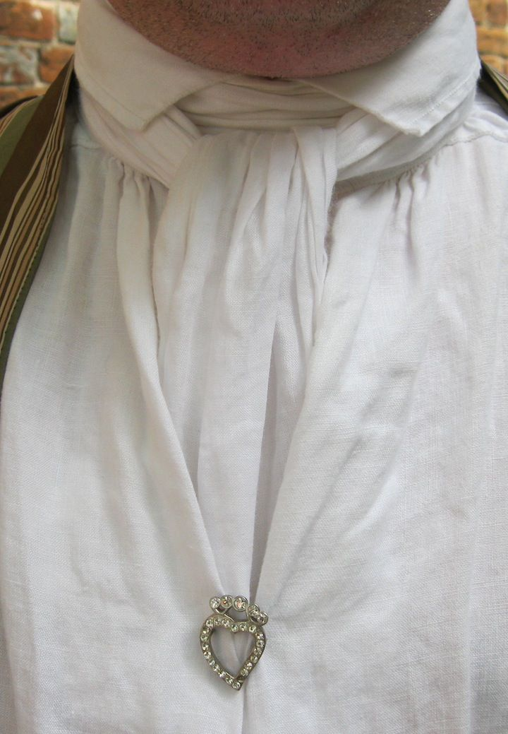Men's shirts in the 18th c didn't button down the front, but pulled over the head. Wealthy gentlemen closed the front opening with fancy shirt buckles; March wore a heart much like this, except with rubies.