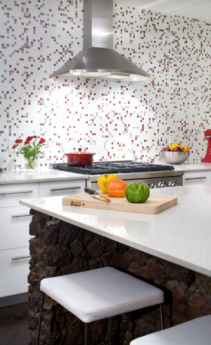 #cocina #conestilopropio: cocina blanco con un azulejo muy alegre en tonos grises y rojos, accesorios a juego y el elemento destacado: para la isla se utiliza roca volcánica.