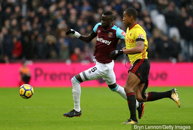 Cheikhou Kouyate of West Ham United and Marvin Zeegelaar of Watford battle for the ball during the Premier League match between West Ham United and Watford at London Stadium on February 10,...