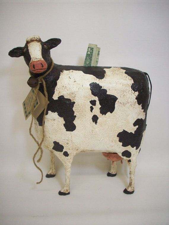 Diese coole Kuh-Bank steht 13 Zoll hoch, ist 10 Zoll lang und ungefähr 4 1/2 Zoll tief. Sie besteht aus vielen Schichten einer papier Pappmache/Sägemehl-Mischung über 2 Styropor-Schalen und einige sehr schwere Draht geformt. Sie hat lackiert, gebeizt versiegelt und worden.  Sie trägt eine einfache Jute Krawatte und rostige Glocke um den Hals.  Sie hat einen Schlitz in der Spitze von ihrem Rücken für Münzen. Ihre Euter wird gebildet, um eine große herausnehmbare Cork Wenn Sie brauche...