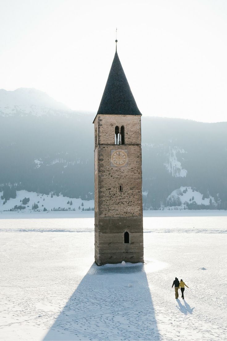 A Bell tower in the middle of a frozen Lake at Reschensee, Italy, South Tirol