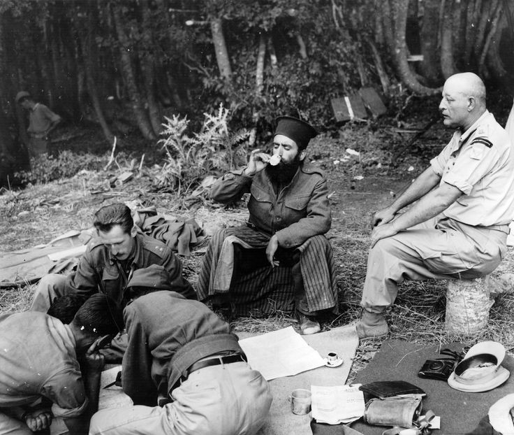 In the mountains of Greece sometime between 1946 and 1948 during the communist insurgency: Communist guerrillas are reading a map while a Greek Orthodox priest fighting alongside them is having his Turkish coffee, always drunk in a small cup like the one he is using. A foreign military observer on the right is -- what else?-- observing.