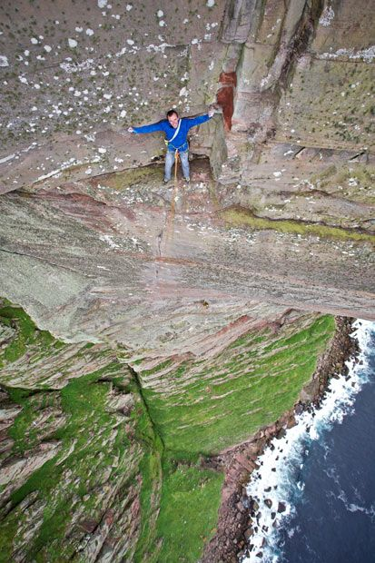 Daredevil Dave MacLeod perches on a rock face 1,000 feet up the world's hardest sea cliff climb. The Scotsman became the first person to freeclimb St John's Head on the Isle of Hoy, Scotland - widely believed to be the world's hardest sea cliff climb. He took time out half way up to check out the breathtaking views from a two-foot wide ledge. Picture: LUKASZ WARZECHA/CATERS NEWS