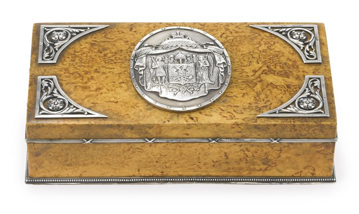 A Fabergé silver-mounted wood table cigar box, workmaster Anders (Antti) Nevalainen, St. Petersburg, 1898-1908, rectangular, the case veneered with birch, the hinged cover applied with scrolling floral mounts, centered with a cast and chased oval with the central elements of the Russian Imperial Seal (Gosudarstvennyi gerb), the rim with ribbon-tied reeded mounts and the base with beaded mount, struck with workmaster's initials, Fabergé in Cyrillic with Imperial warrant, 84 standard