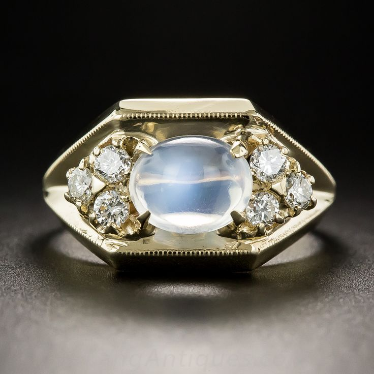 A luminous high-profile moonstone glistens and glows with a distinct blue flash between trios of bright white and sparkling round diamonds in this stylishly tailored just-for-fun ring sturdily crafted in gleaming 10K yellow gold. .35 carat total diamond weight. Currently ring size 7 1/4.