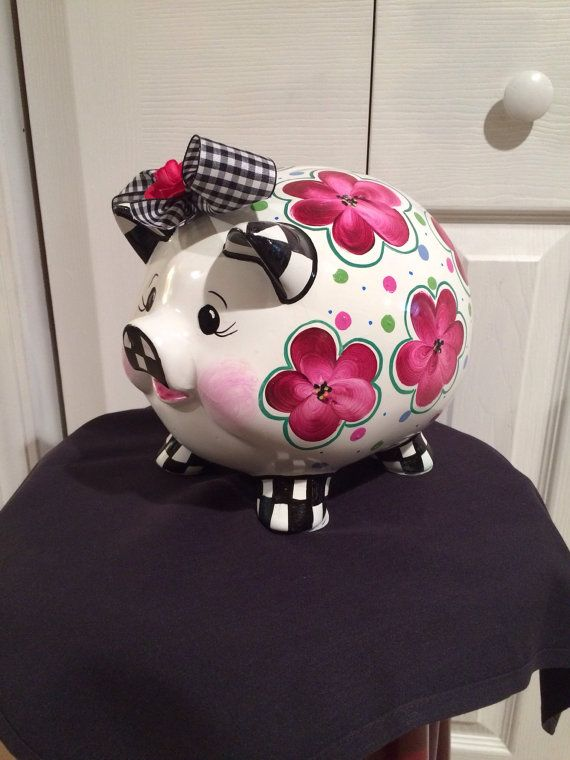 This adorable piggy bank is painted with flowers, dots and black and white check. Painted in shades of pink, berry, green and purple, this