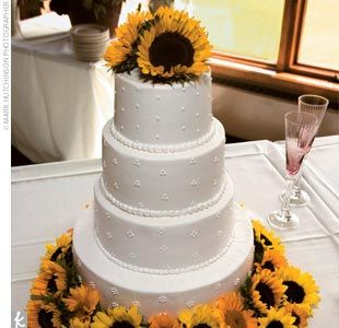 A sweet cream wedding cake served as a decadent dessert, topped with Swiss dots and sunflowers.