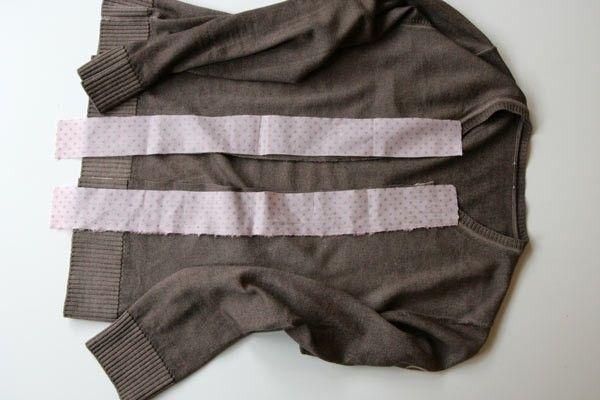 pull-veste-1Vérifiez que vous avez prélaver le tissu que vous allez rajouter comme parementure. Vous ne voudriez pas qu'il rétrécisse. Coupez le pull en son milieu. Vous pouvez tracer un trait au feutre effaçable et évitez de trop tirer sur la maille quand vous la coupez. Mesurez et coupez les bandes de tissu : elles doivent faire 5 cm de large et être 5 cm plus longues que la hauteur du pull en son milieu.