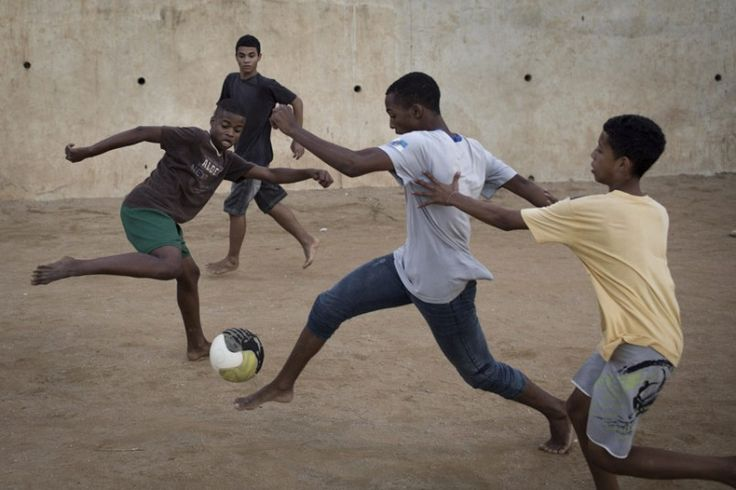 Youths play soccer in the Sao Carlos slum in Rio de Janeiro, Brazil. As opening day for the World Cup approaches, people continue to stage protests, some about the billions of dollars spent on the World Cup at a time of social hardship, but soccer is still a unifying force. The international soccer tournament will be the first in the South American nation since 1950.