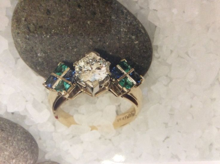 wide marquise diamond flanked by a square grid of princess cut saphires and emeralds