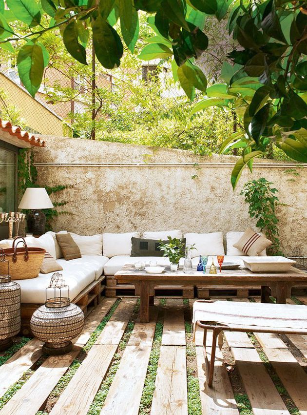 ChicDecó | Stylish Spanish courtyard with seating area built with pallets and decorated with raffia cushions and gorgeous wired lanterns