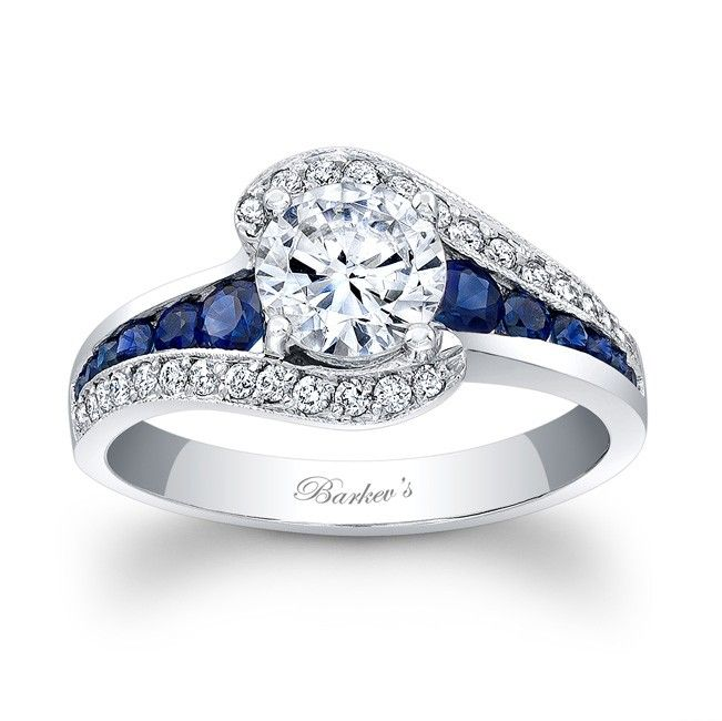 Blue Sapphire Engagement Ring - 7898LBSW - This classic white gold sapphire and diamond engagement ring features a prong set round diamond center. The shoulders split and curve up to cradle the center with pave set diamonds, while channel set saphiress grace the center on the sides.      Also available in rose, yellow gold, 18k and Platinum.