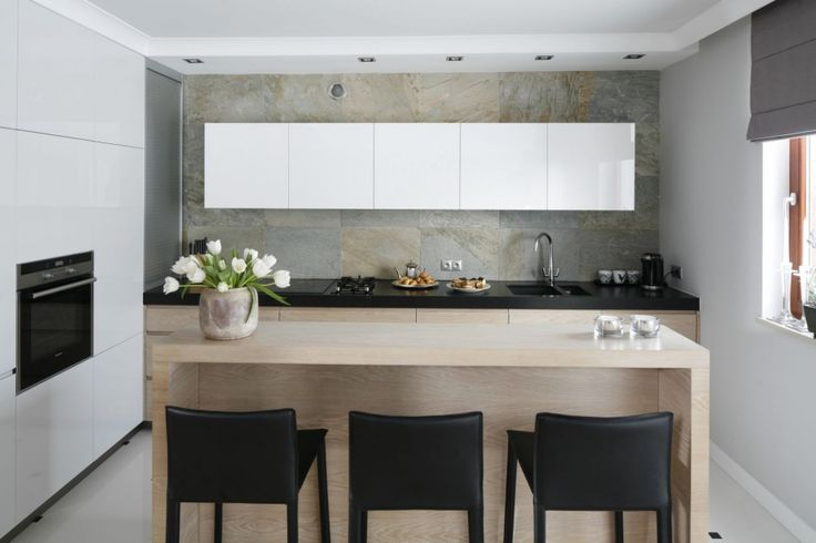 Otwartą na salon kuchnię urządzono w chłodnej palecie barw. Biel doskonale komponuje się tu z jasnym, naturalnym drewnem oraz szarością kamienia, którym wyłożono jedną ze ścian. Projekt Magdalena Smyk. Fot. Bartosz Jarosz.