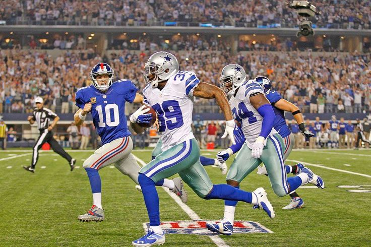 Dallas Cowboys #39 Brandon Carr sprints past Manning to the end zone for the game deciding score.