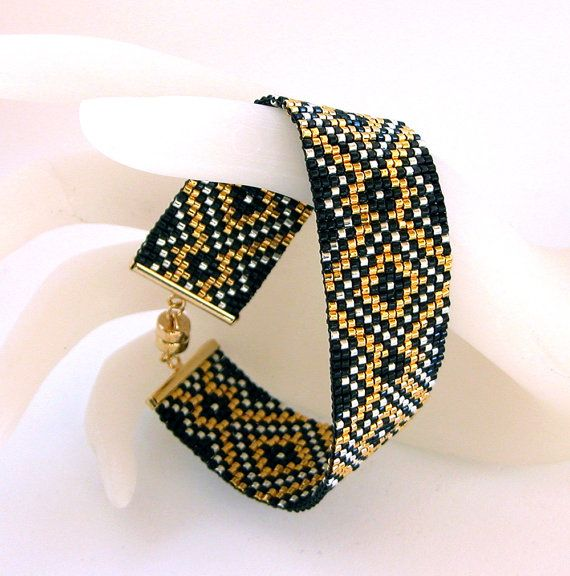 This 7 1/4 inch (18.5cm) bracelet was created on a bead loom using Delica cylinder beads in a design I created myself. The main colors are 24k plated gold, silver and black. It is 7/8 inches (2.3cm) wide and will easily fit a 6 1/2 -7 inch wrist. It is very easy to put on and take off because of the magnetic clasp.     MEMBER - beadsforever
