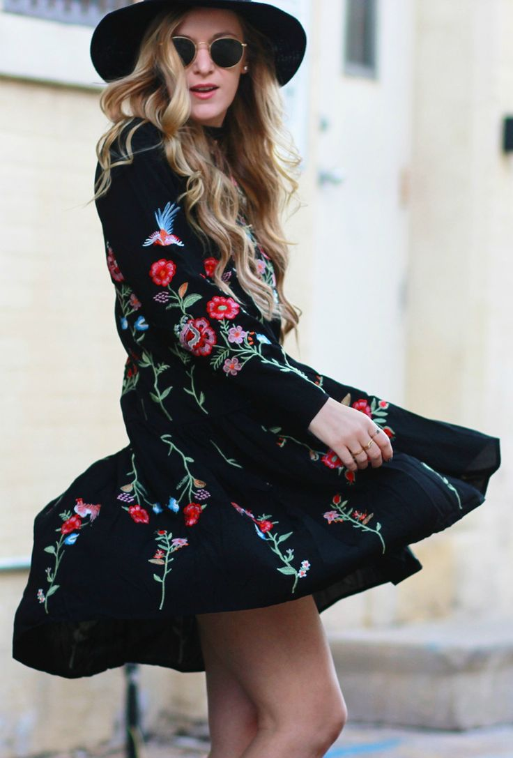 Casual boho fall outfit styled with black long sleeve embroidered dress, block heel booties, round Rays Bans, and black hat