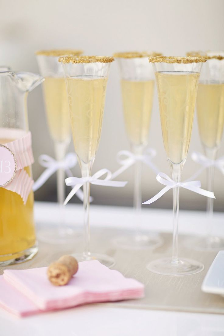 Little white bows and edible gold sprinkles added a festive touch to the glasses. For these, we mixed Izze Sparkling Peach juice with champagne.