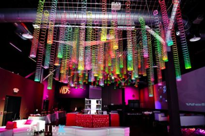 Multi-colored neon slinkys create this interesting ceiling treatment from Jersey Street Furniture and Jamie K Photography