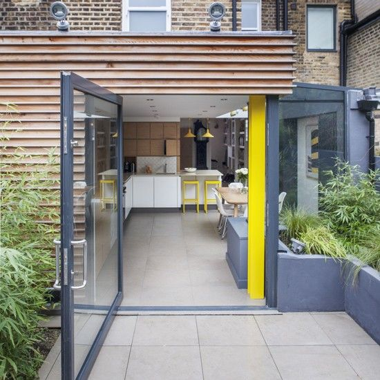 This modern kitchen extension was inspired by the owners favourite nightclub in manchester. The injection of colour adds personality and wooden units mirror the outside of the extension and add warmth. By using the same floor tiles inside and out and the way the huge door swings right open, creates a seamless flow between the kitchen and garden which is perfect for family life and entertaining. http://www.housetohome.co.uk/house-tour/picture/be-inspired-by-a-1980s-yellow-and-black-kitchen