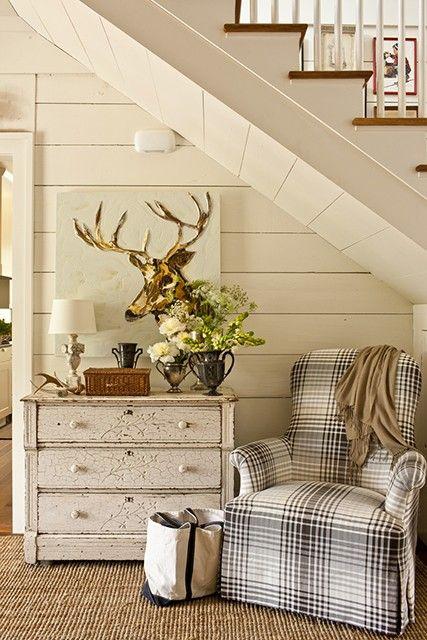 Staircase, plaid chair, dresser, deer art