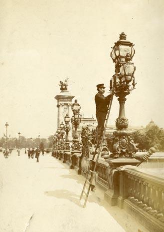 Paris. Allumeur de réverbère sur le pont Alexandre III. 1901 env.