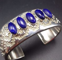 """The gemstones are secure in smooth bezel, on a foundation of heavy gauge cast sterling silver. The cuff features a Navajo rug eye dazzler motif. SIGNED: JR Tolino (Navajo). MEASUREMENTS: Interior of the cuff measures 5 3/8"""". 