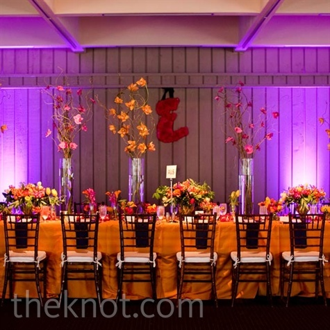 Orange tablecloths gave a jolt of energy to the room. A mix of tall orchid arrangements and low centerpieces lent the head table some extra dimension.