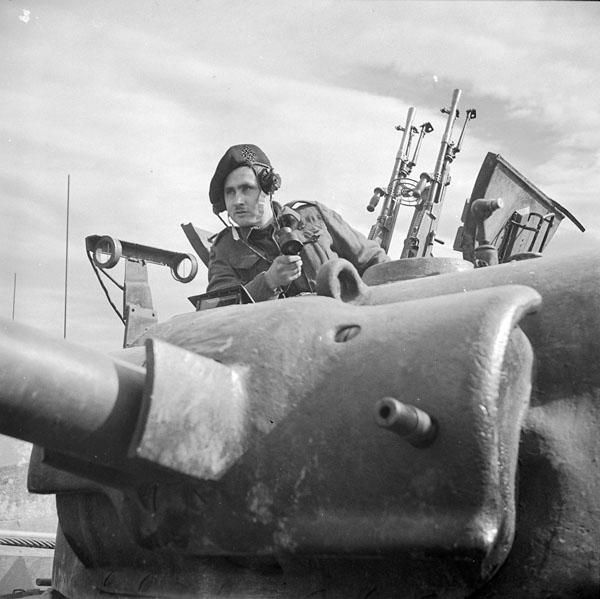 An unidentified crew commander of the 8th Princess Louise's (New Brunswick) Hussars in the hatch of his Sherman tank giving firing orders to his gunner during a predicted mass tank firing exercise, Italy, March 2nd 1944. Two Bren machine guns are mounted directly behind the crew commander.