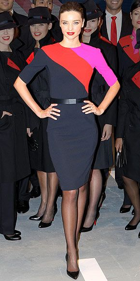 Miranda Kerr in navy dress with bold pink and red horizontal stripes attending a Qantas event in Sydney, Australia