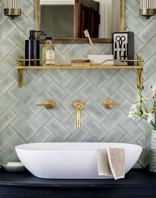 The elegant shelf in this green tiled bathroom coordinates perfectly with the brass taps below, giving the space a considered, elegant feel