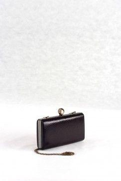 Τσάντα φάκελος μαύρος, διακριτικά μεταλλικό χρώμα, υφή υφάσματος.  Κλασική πολυτέλεια με ξεχωριστό κούμπωμα.  Περιλαμβάνει μεγάλη και μικρή αλυσίδα για κρέμασμα στο χέρι ή στον ώμο. Εσωτερικά μαύρη σατέν φόδρα, 1 μεγάλος ενιαίος χώρος.