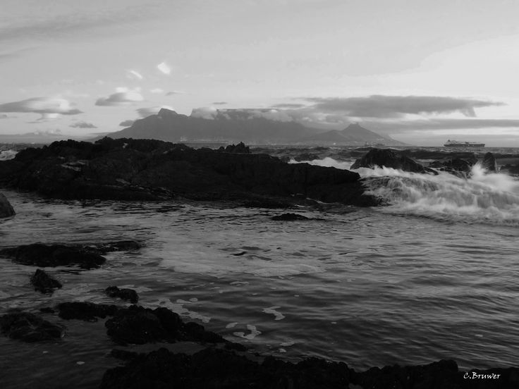 Click on image to view non sample image. Black and white image of Table Mountain in Cape Town South Africa. Dynamic wave and rock setting compliments the mountain nicely.