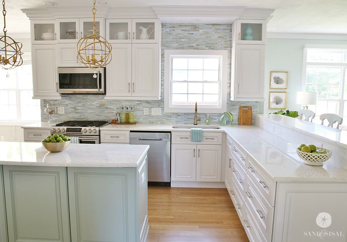 This amazing Coastal Kitchen Makeover has white kitchen cabinets, a seaglass blue coastal backsplash, mixed metals and weathered oak floors. See the before!