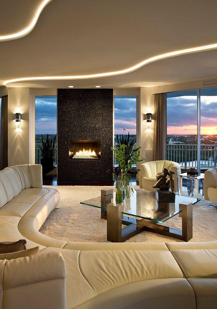 Sala de estar extremamente elegante, com paredes de vidro, lareira e uma decoração impecável.