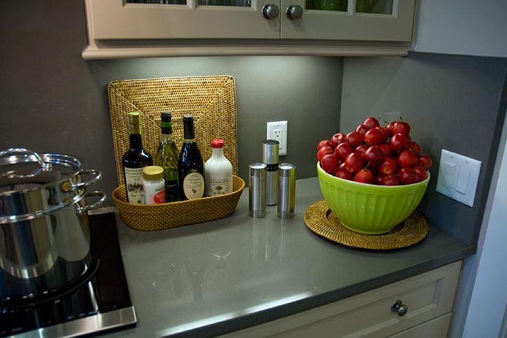 The countertops are manmade quartz done in the color of cement. This eco-friendly material is stain-resistant, heat-resistant and anti-microbial. This material is carried up onto the backsplash, simplifying the room's style and functionality.