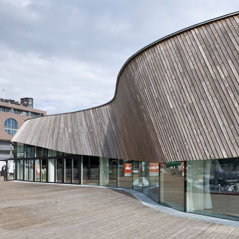 A wave of timber undulates around the eaves of a waterside restaurant in Oslo by Danish architects MAPT.