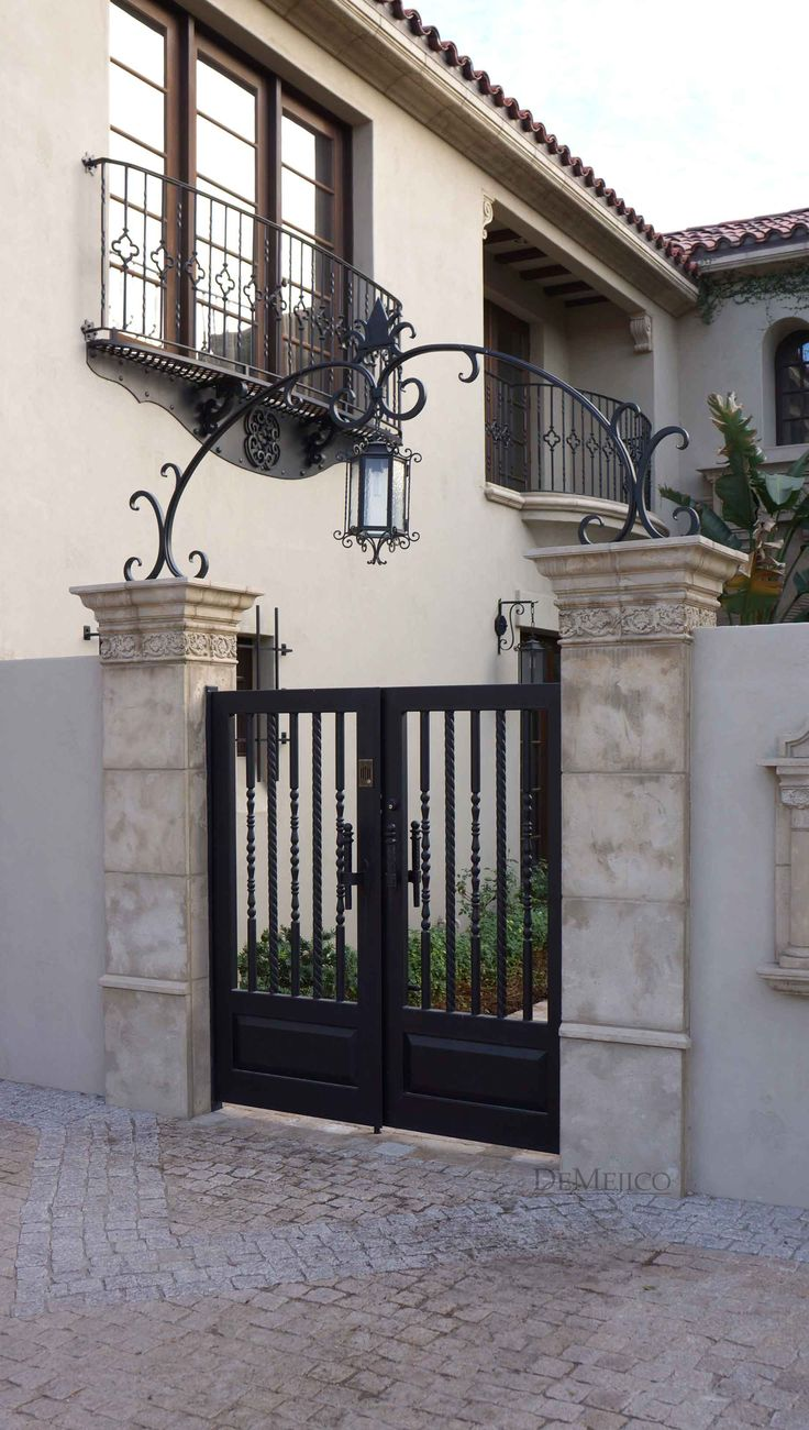 A classic and custom wrought iron entry gate, complimented by an accent arch, is an eye catching feature added to this Spanish style home.