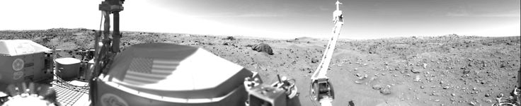 Sand Dunes, Rocks, and Flags  Sand dunes and large rocks are revealed in this panorama of Mars in the first photograph taken by Viking l's Camera 1 on July 23, having landed on July 20, 1976. The horizon is approximately 3 kilometers (2 miles) away. The late afternoon sun is high in the sky over the left side of the picture. The support struts of the S-band high-gain antenna extend to the top of the picture....