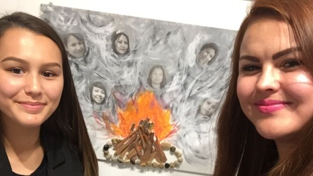 Aureya Ayopte, left, a 14-year-old student at Bob Edwards School in Calgary, stands with Tatsikiisaapo'p Middle School art teacher Andrea Fox in front of a work of art created by Ayopte at the Studio C Prospect gallery in Calgary.