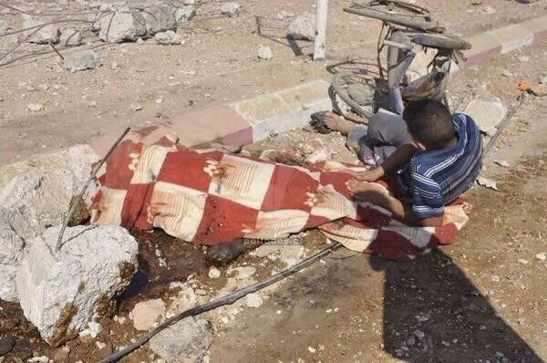 Gaza man sitting next to the body of his handicapped  sister after she was killed by the nazis Israeli zionest.