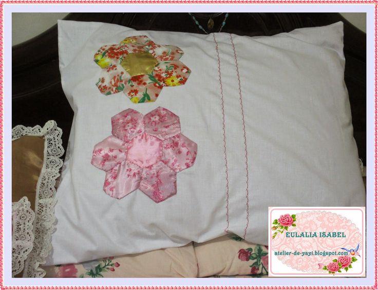 Funda de almohadón,en tela blanca,  con apliques de tela y bordado en máquina, en un lado.