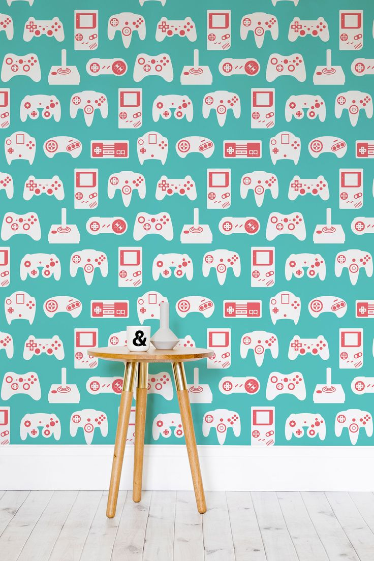 Relive your childhood obsession with this retro gaming wallpaper. Striking turquoise tones contrast with the punchy peach details of classic gamepads. Perfect for modern living room spaces looking for an injection of colour.