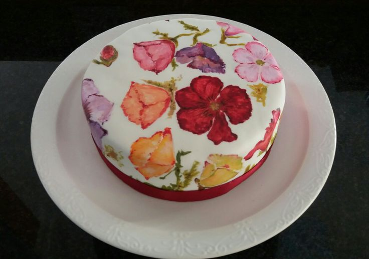 Skilfully hand-painted brightly coloured Iceland poppies making merry on light fruit cake studded with glazed fruit  soaked in brandy, rum and sherry.